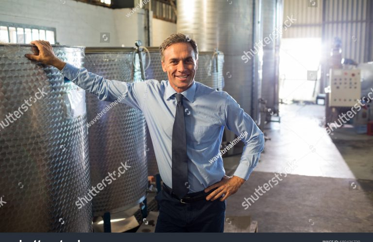 stock-photo-portrait-of-happy-manager-standing-near-oil-refinery-in-factory-680436730